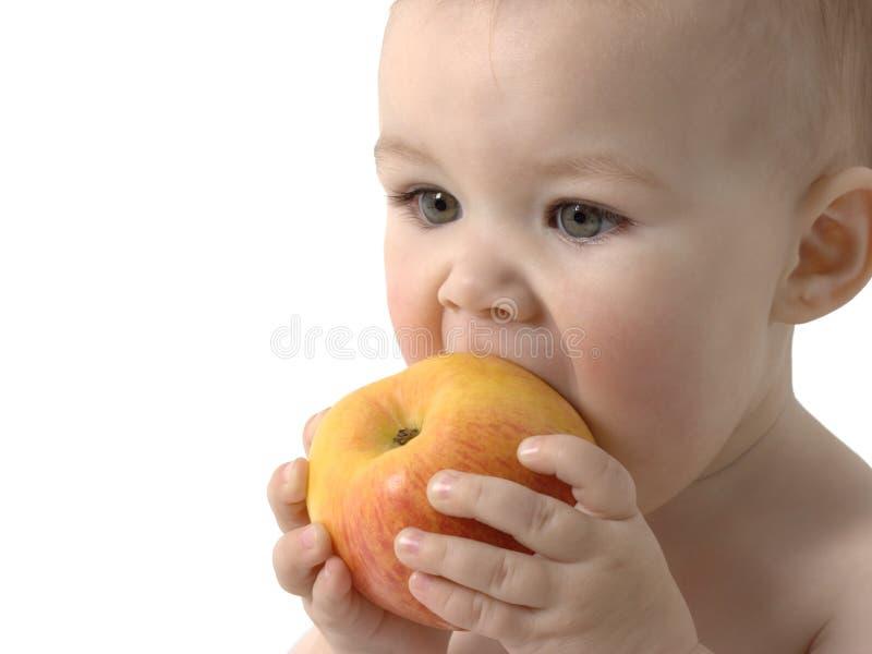 El niño lindo come la manzana fotografía de archivo libre de regalías