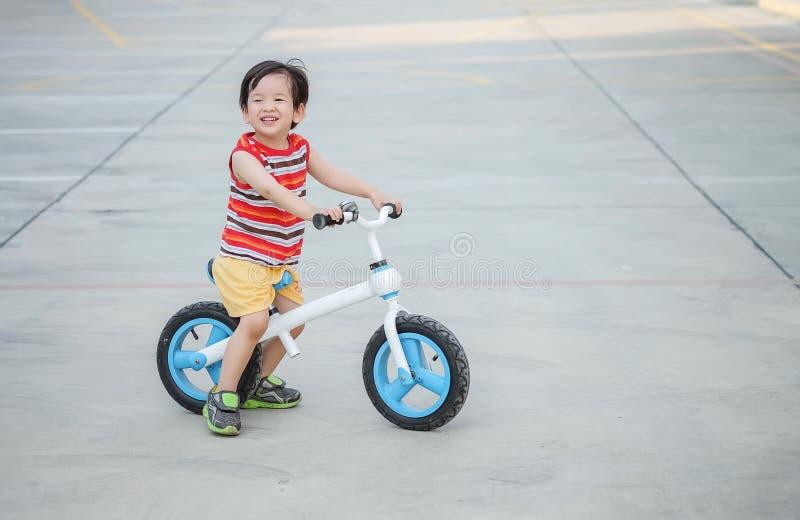 El niño lindo del primer con paseo de la cara de la sonrisa una bicicleta en piso del cemento en el aparcamiento texturizó el fon fotos de archivo libres de regalías