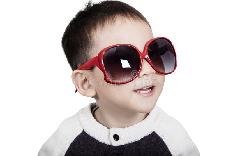 El niño lindo elegante está llevando las gafas de sol y la sonrisa fotografía de archivo