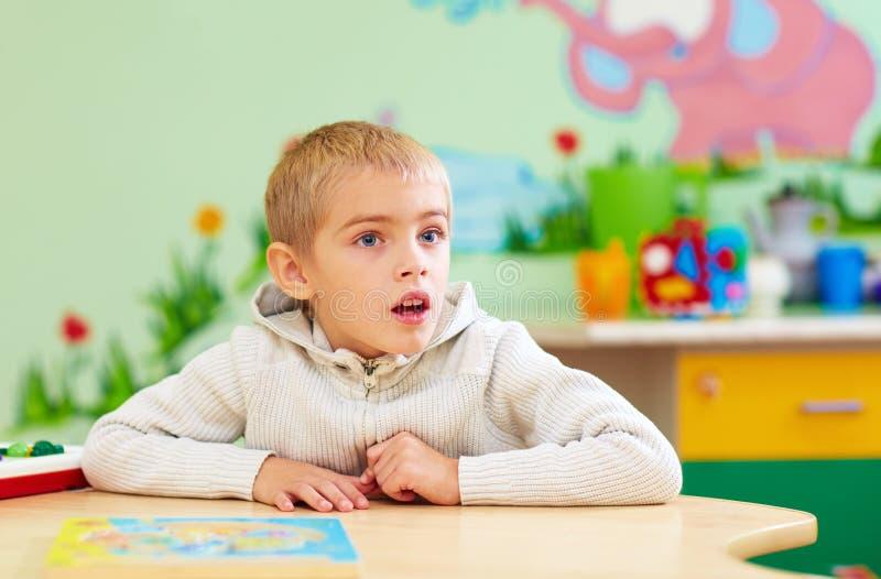 El niño lindo, muchacho con el special necesita en centro de rehabilitación foto de archivo