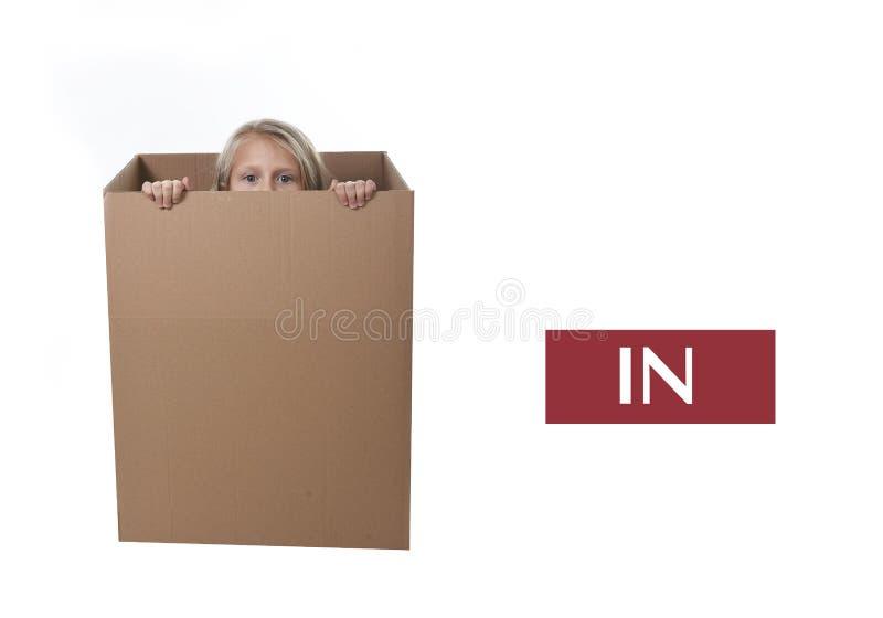 El niño lindo y dulce del pelo rubio hiden en la caja de cartón aislada en el fondo blanco en el aprendizaje de preposiciones ing imagenes de archivo