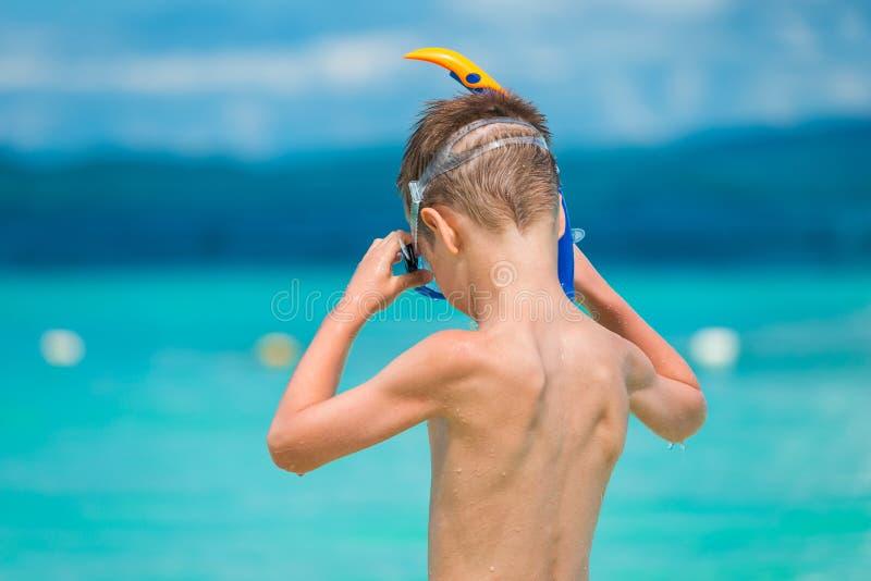 El niño lleva una máscara que bucea en la costa imagen de archivo