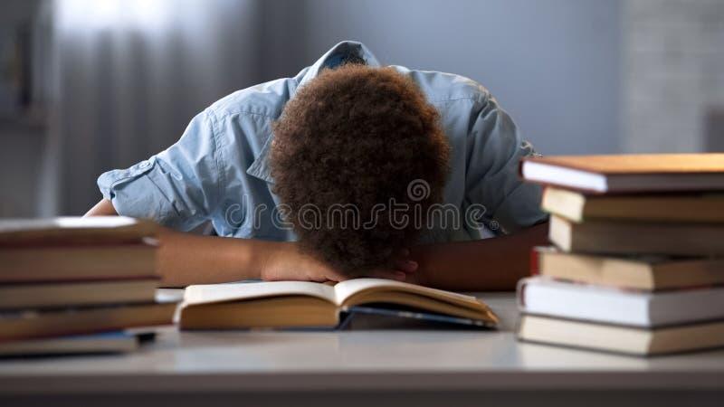 El niño masculino que dormía en la tabla cansó de los libros de lectura, haciendo la porción de preparación foto de archivo libre de regalías
