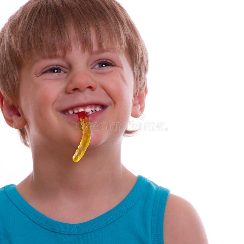 El niño mastica osos gomosos y ríe fotografía de archivo