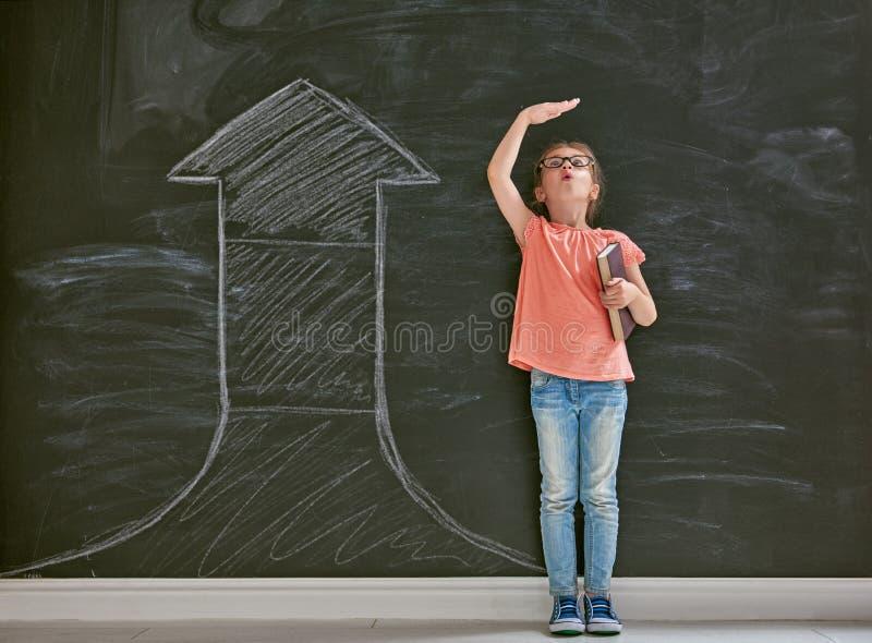 El niño mide el crecimiento foto de archivo