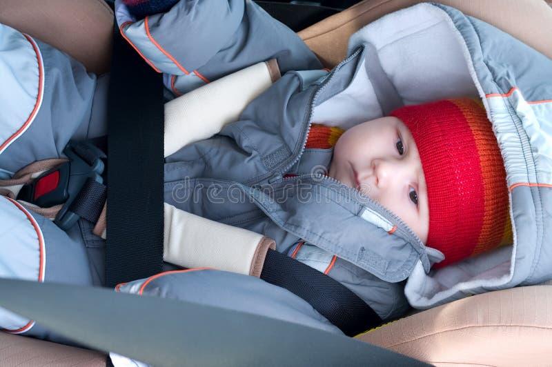 El niño miente en asiento de coche foto de archivo