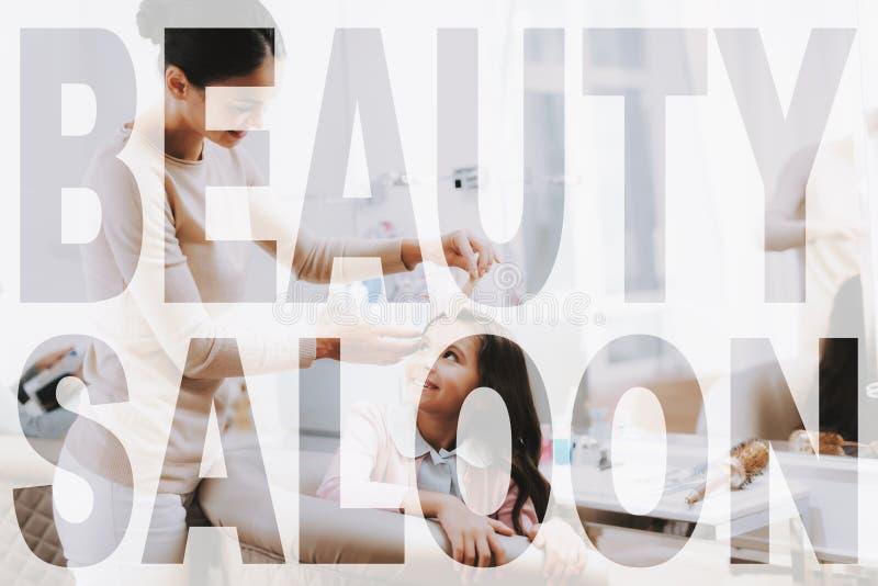 El niño mira al peluquero mientras que ella se peina el pelo foto de archivo
