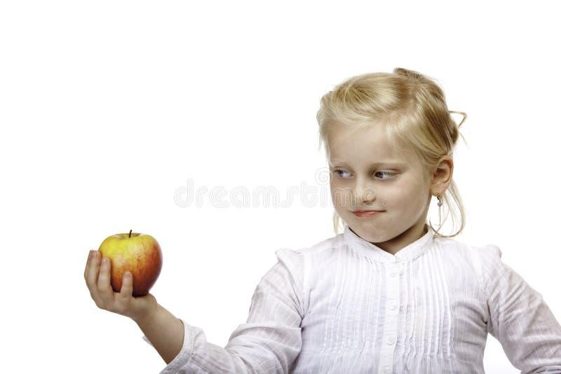 El niño mira contemplativo la fruta sana (la manzana) imagen de archivo