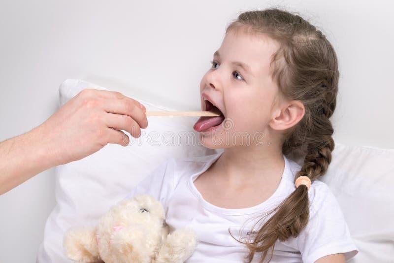 El niño mira la garganta con un palillo de madera, sin salir de la cama fotos de archivo libres de regalías