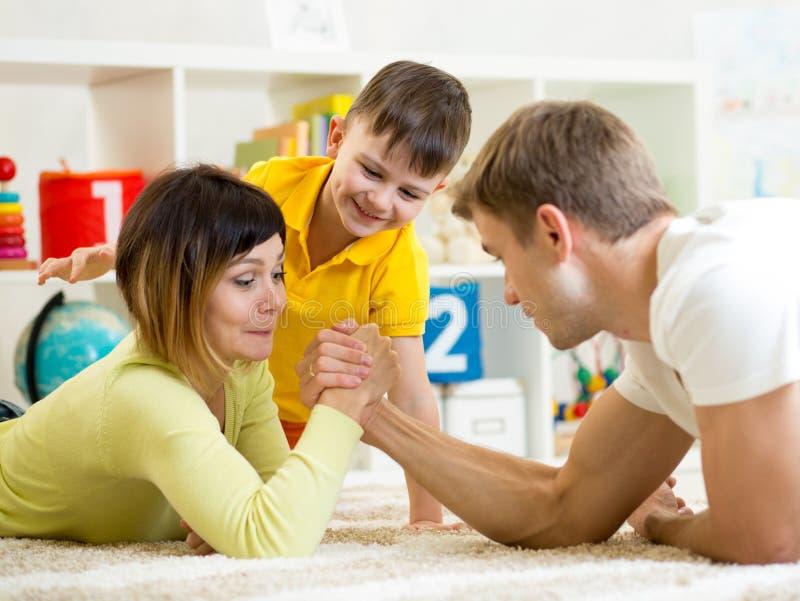 El niño mira su papá y mamá que compiten en fuerza física fotos de archivo
