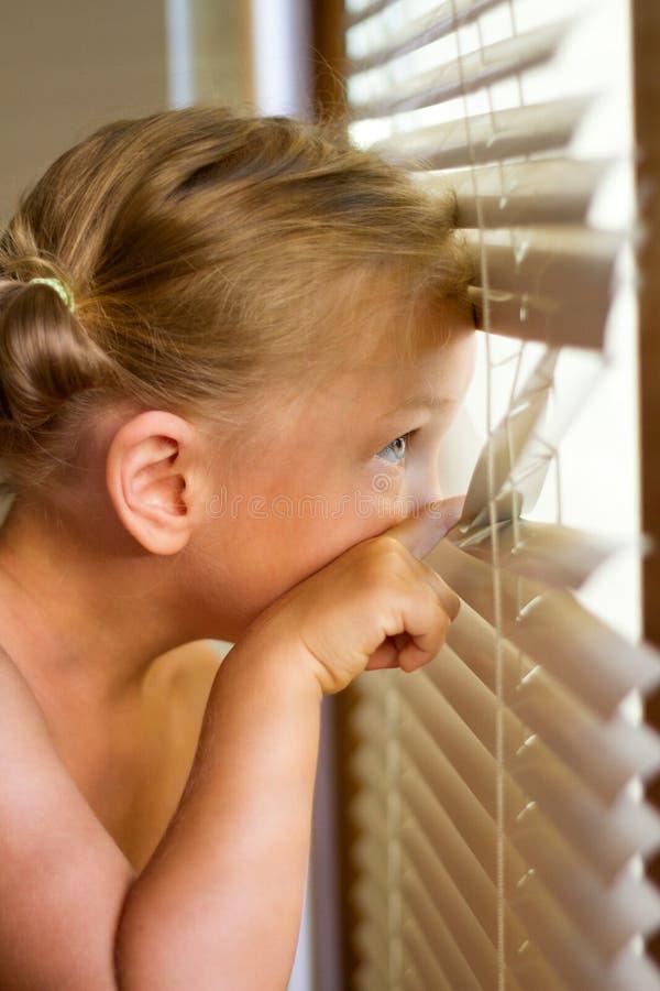 El niño mira a través de las persianas fotos de archivo