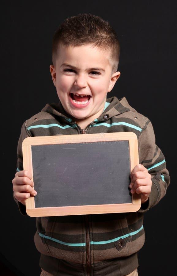 El niño muestra una pizarra imagenes de archivo