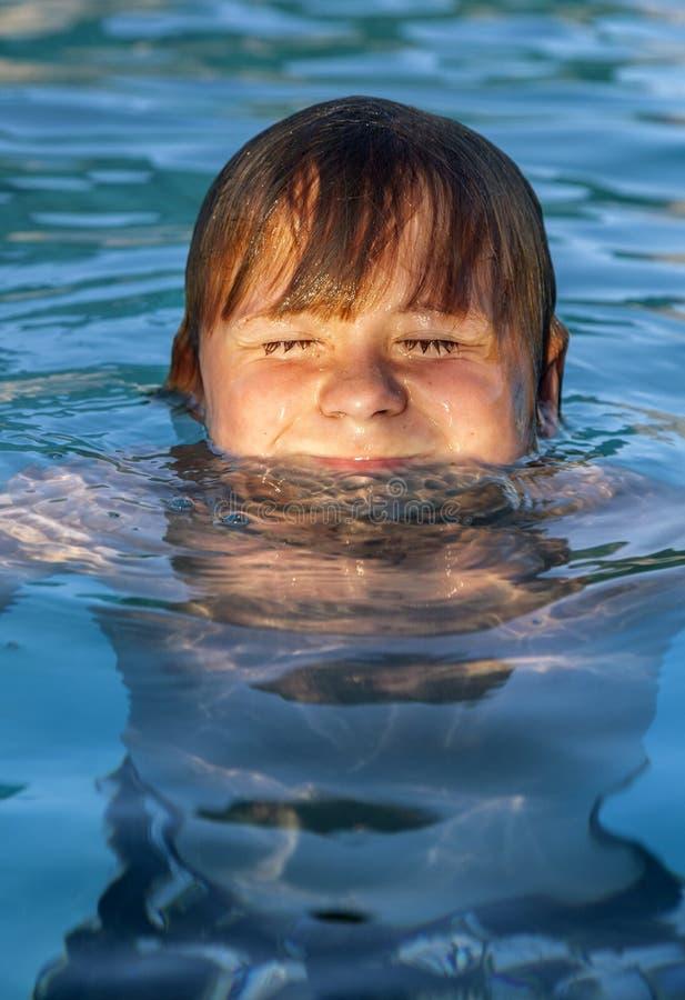 El niño nada en la piscina al aire libre imágenes de archivo libres de regalías