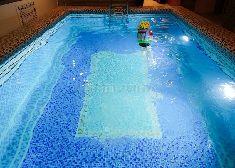 El niño nada en la piscina Piscina en la sauna con agua clara Ornamento de baldosas cerámicas imagenes de archivo