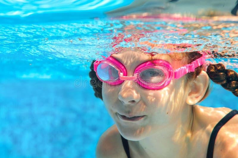 El niño nada en la piscina subacuática, muchacha activa feliz en gafas se divierte en agua, deporte del niño el vacaciones de fam imagen de archivo