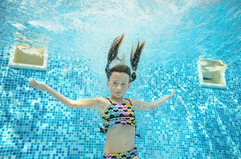 El niño nada en la piscina subacuática, muchacha activa feliz se zambulle y se divierte debajo del agua, deporte del niño imagenes de archivo