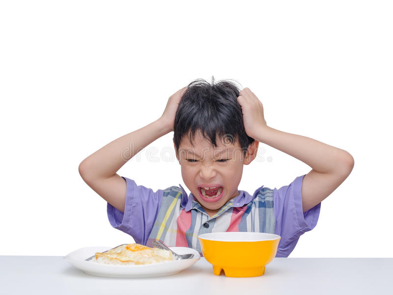 El niño no quiere comer la comida para el almuerzo imagenes de archivo