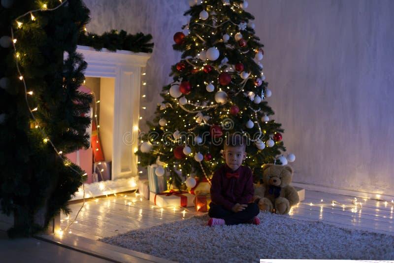 El niño pequeño abre la guirnalda del árbol de navidad del Año Nuevo de los regalos de Navidad imagenes de archivo