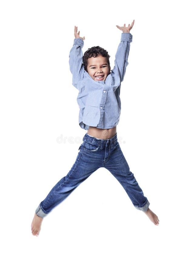 El niño pequeño afroamericano lindo salta aislado encendido imagenes de archivo