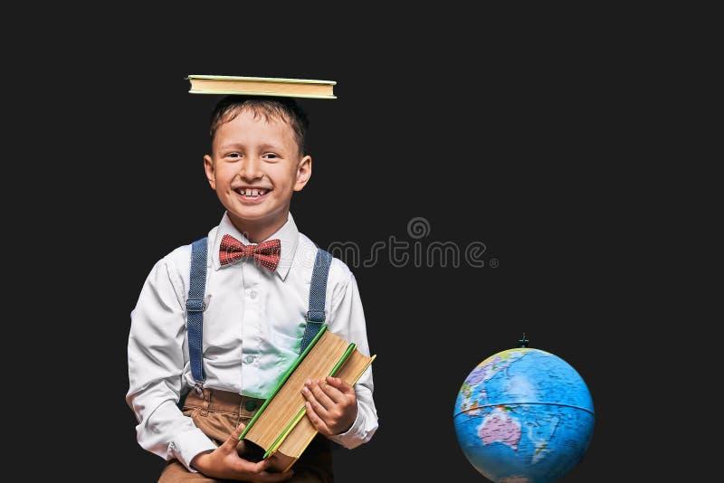 El niño pequeño alegre se coloca en un fondo negro con un libro en sus manos un niño feliz aprende leer un libro Literatura de la fotos de archivo