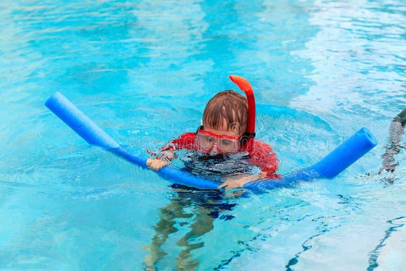 El niño pequeño aprende nadar solamente con los tallarines de la piscina imagen de archivo