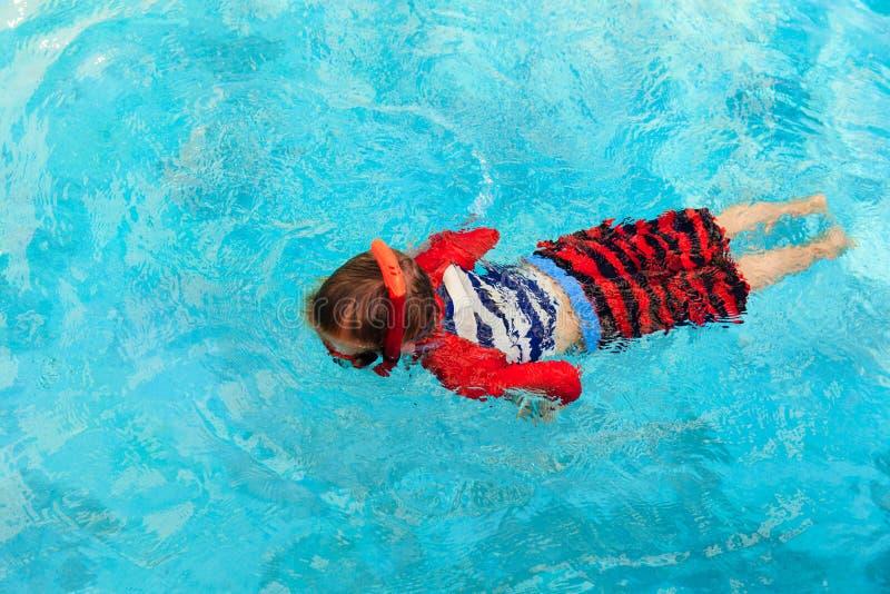 El niño pequeño aprende nadar solamente en la piscina foto de archivo libre de regalías