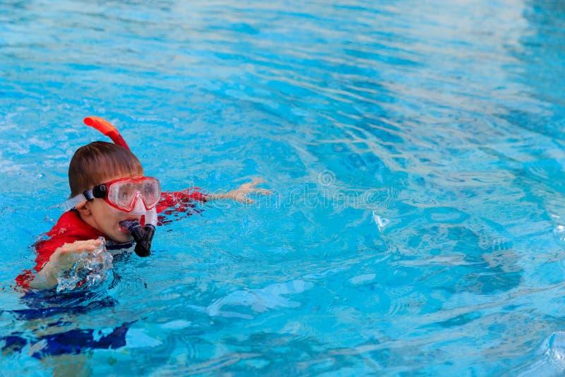 El niño pequeño aprende nadar solamente en la piscina imagen de archivo