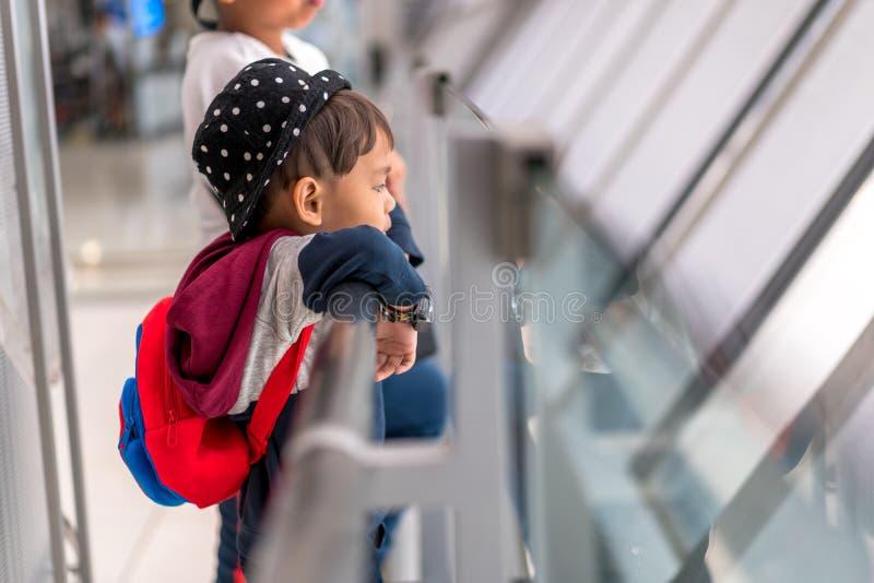 El niño pequeño asiático 3 años lleva el embarque que espera del bolso al vuelo en pasillo terminal del tránsito del aeropuerto d foto de archivo