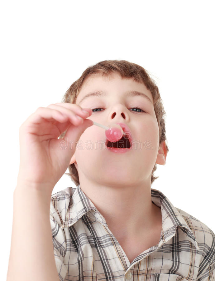 El niño pequeño aspira el lollipop rosado aislado imagenes de archivo