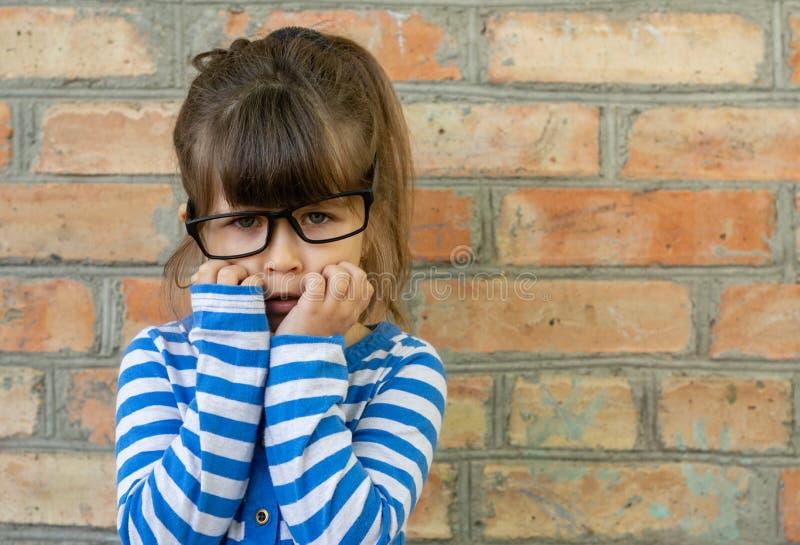 El niño pequeño asustado del niño en la camiseta blanca expresa placer en una pared de ladrillo vacía en blanco fotos de archivo libres de regalías