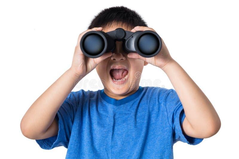 El niño pequeño chino asiático que sostiene los prismáticos con la boca se abre imagenes de archivo