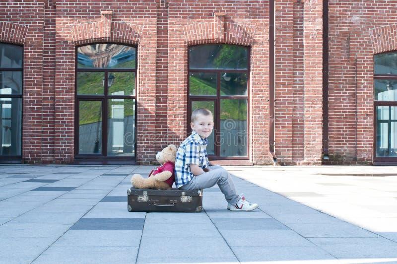 El niño pequeño con el juguete del oso de peluche se está sentando en la maleta imagen de archivo