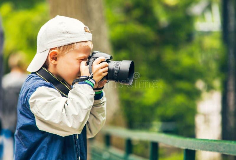 El niño pequeño con la cámara de la foto hace un lanzamiento fotografía de archivo