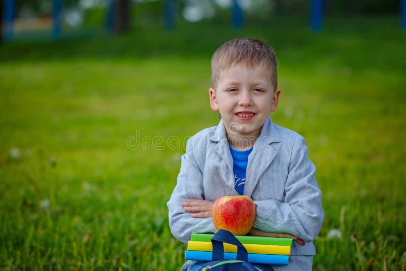 El niño pequeño con la pila de libros y la manzana roja en la naturaleza ponen verde el fondo fotografía de archivo