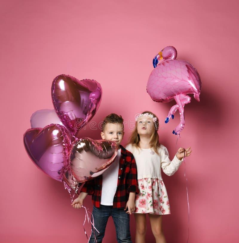 El niño pequeño con los globos del corazón del color y la niña con el globo del flamenco son la fiesta de cumpleaños o el otro dí imagenes de archivo