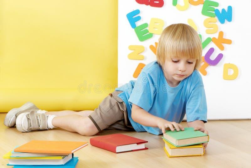 El niño pequeño con los libros foto de archivo