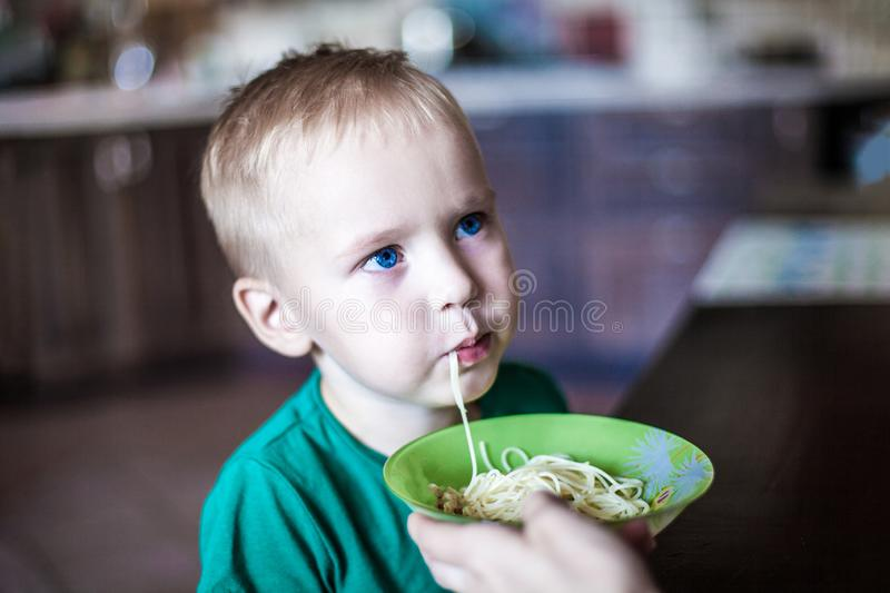El niño pequeño con los ojos azules brillantes en t-cortocircuito verde come los espaguetis del cuenco verde fotos de archivo libres de regalías