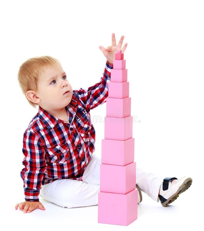 El niño pequeño construye una pirámide en el Montessori imagenes de archivo