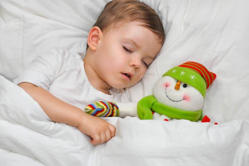 El niño pequeño del ute del ¡de Ð está durmiendo en el lino blanco con su muñeco de nieve preferido del juguete imagenes de archivo