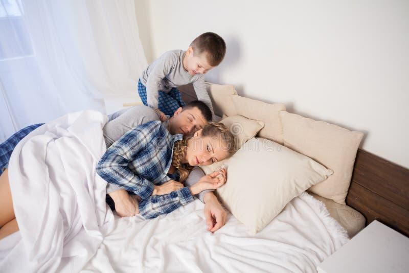 El niño pequeño despierta por la mañana, padres imágenes de archivo libres de regalías