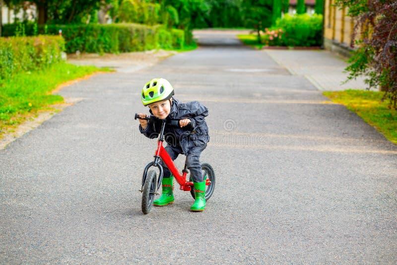 El niño pequeño en bici verde del casco y de la balanza funciona con la bici Childho imagen de archivo libre de regalías
