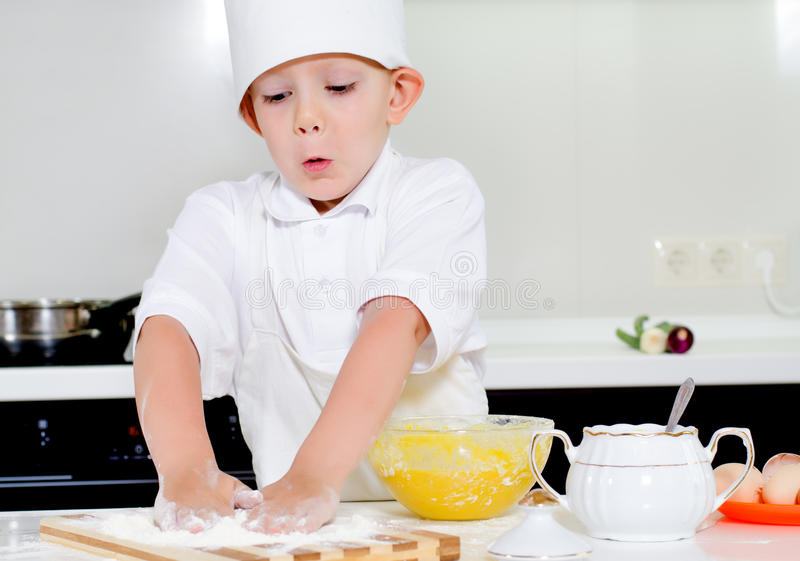El niño pequeño en cocineros uniforma la hornada en la cocina foto de archivo