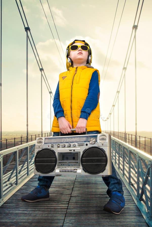 El niño pequeño en el estilo del hip-hop sostiene una grabadora del vintage El golpeador joven Refresque el rap DJ Equipo estéreo imagenes de archivo
