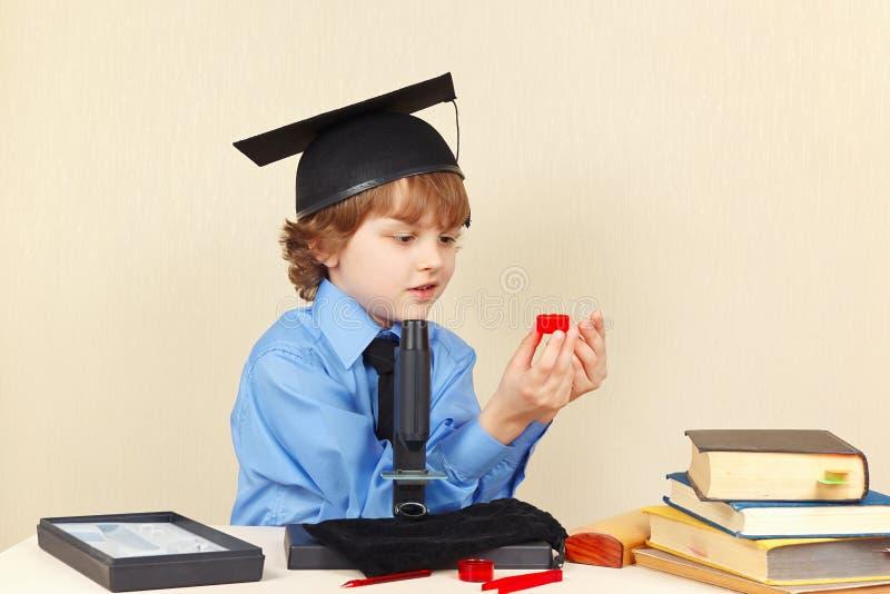 El niño pequeño en sombrero académico conduce la investigación con el microscopio foto de archivo libre de regalías