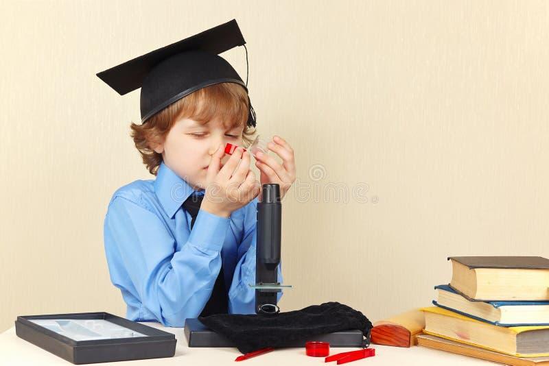 El niño pequeño en sombrero académico ve los tarros para la investigación al lado del microscopio fotografía de archivo libre de regalías