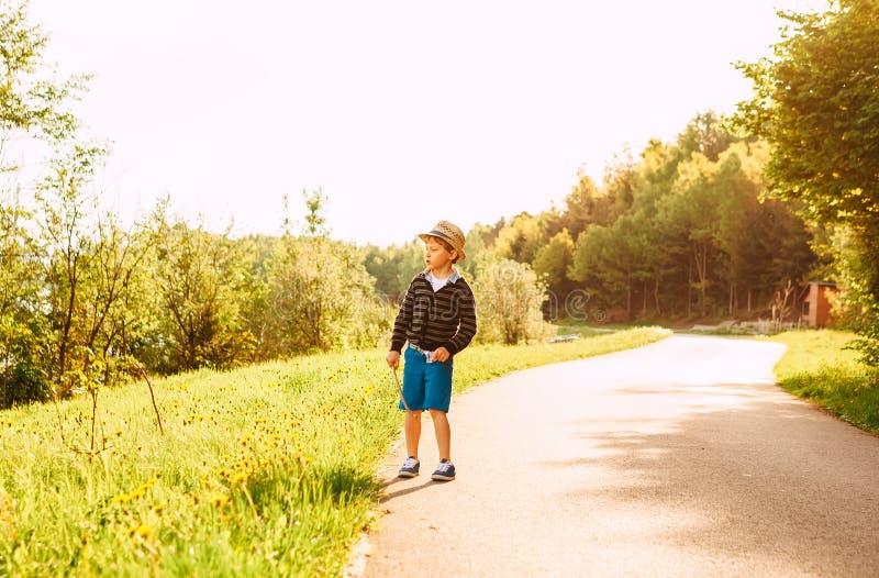 El niño pequeño en sombrero de paja camina en el camino del campo en el verano foto de archivo