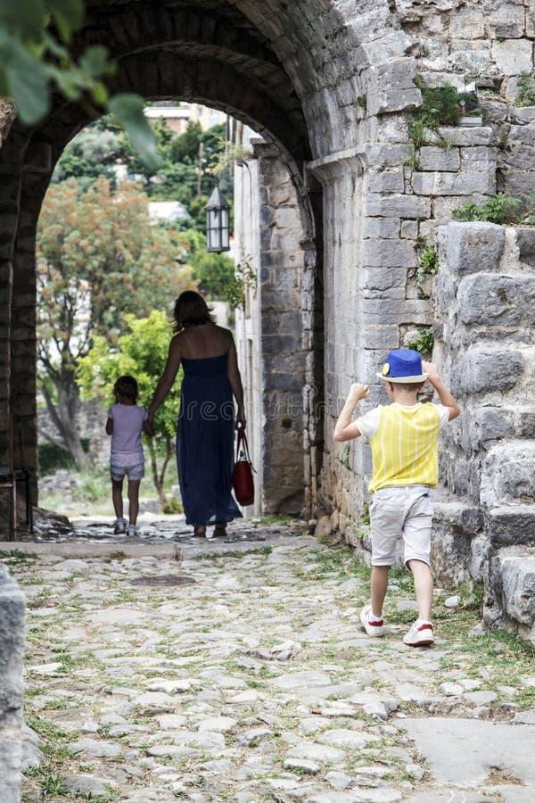 El niño pequeño en un sombrero azul alcanza su madre y hermana g fotos de archivo
