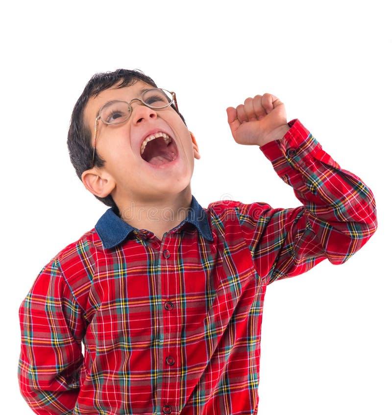 El niño pequeño en vidrios expresa su alegría con su puño fotografía de archivo libre de regalías