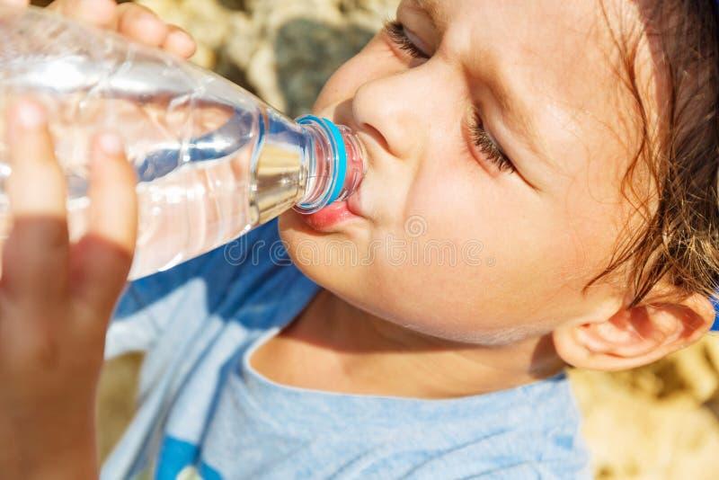 El niño pequeño es agua potable foto de archivo libre de regalías