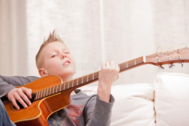 El niño pequeño es muy bueno en tocar la guitarra imagen de archivo libre de regalías